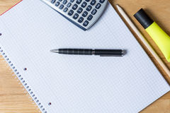 Trabaje el escritorio con el cuaderno de notas, la calculadora y el biro en la tabla de madera imagen de archivo libre de regalías
