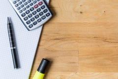 Trabaje el escritorio con el cuaderno de notas, la calculadora y el biro en la tabla de madera imagen de archivo