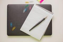 Trabaje la mesa con el cuaderno, las fuentes y el ordenador portátil cerrado Fotos de archivo libres de regalías