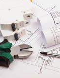 Trabaje las herramientas, el fusible eléctrico y los rollos de diagramas en el dibujo de construcción de la casa Imagen de archivo libre de regalías