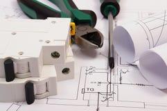 Trabaje las herramientas, el fusible eléctrico y los rollos de diagramas en el dibujo de construcción de la casa Imágenes de archivo libres de regalías