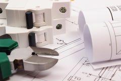 Trabaje las herramientas, el fusible eléctrico y los rollos de diagramas en el dibujo de construcción de la casa Foto de archivo