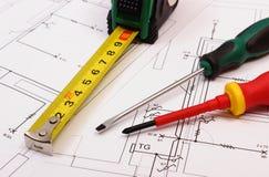 Trabaje las herramientas en el dibujo de construcción eléctrico de la casa Fotos de archivo libres de regalías