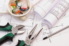 Trabaje las herramientas, la caja eléctrica con los cables y el dibujo de construcción eléctrico Fotos de archivo