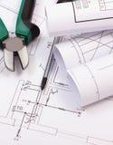 Trabaje las herramientas y los rollos de diagramas en el dibujo de construcción de la casa Foto de archivo libre de regalías