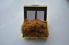 Trabaje a máquina para los cigarrillos de relleno en la tabla con la tapa amarilla y algo de tabaco en él Imagen de archivo libre de regalías