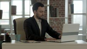 Trabajo acabado hombre de negocios delante de un ordenador portátil metrajes
