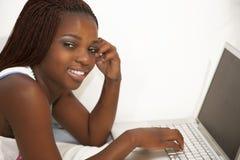 Trabajo adolescente africano en el ordenador portátil y el hablar en una célula pH Imagenes de archivo