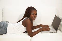 Trabajo adolescente africano en el ordenador portátil y el hablar en una célula pH Fotos de archivo