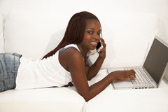 Trabajo adolescente africano en el ordenador portátil y el hablar en una célula pH Fotografía de archivo libre de regalías