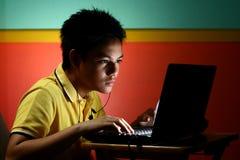 Trabajo adolescente asiático en un ordenador portátil Foto de archivo libre de regalías