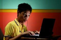 Trabajo adolescente asiático en un ordenador portátil Fotos de archivo libres de regalías