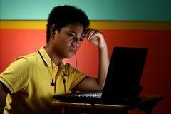 Trabajo adolescente asiático en un ordenador portátil Imagen de archivo