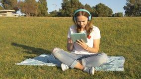 Trabajo adolescente con la tableta en el parque fotos de archivo