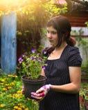 Trabajo adolescente de la muchacha sobre ajardinar el pote del control del diseño del jardín con los pensamientos Imágenes de archivo libres de regalías
