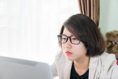 Trabajo adolescente de la mujer en el ordenador portátil en Ministerio del Interior Fotografía de archivo