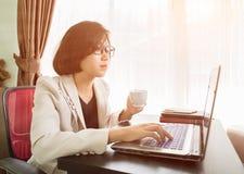 Trabajo adolescente de la mujer en el ordenador portátil en Ministerio del Interior Fotos de archivo libres de regalías