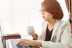 Trabajo adolescente de la mujer en el ordenador portátil en Ministerio del Interior Imágenes de archivo libres de regalías
