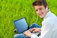 Trabajo adolescente en el ordenador portátil al aire libre. Imágenes de archivo libres de regalías