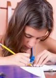Trabajo adolescente latino en su proyecto de la escuela Imagen de archivo libre de regalías