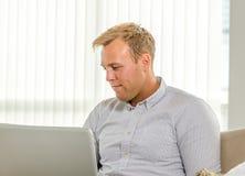 Trabajo adulto joven en el ordenador portátil Foto de archivo libre de regalías
