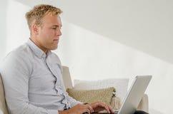 Trabajo adulto joven en el ordenador portátil Imagen de archivo