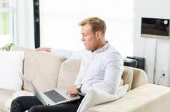 Trabajo adulto joven en el ordenador portátil Fotos de archivo