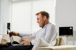 Trabajo adulto joven en el ordenador portátil Fotos de archivo libres de regalías