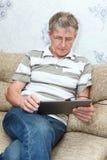 Trabajo adulto maduro con PC de la tablilla Fotos de archivo