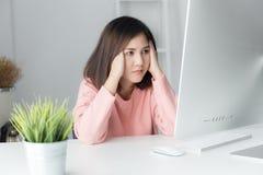 Trabajo agotador de las mujeres asiáticas con un ordenador durante mucho tiempo, de Fotos de archivo