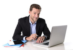 Trabajo atractivo joven del hombre de negocios feliz en el escritorio del ordenador satisfecho y sonrisa relajada Imágenes de archivo libres de regalías