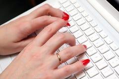 Trabajo caucásico de la mujer sobre una computadora portátil blanca. Foto de archivo