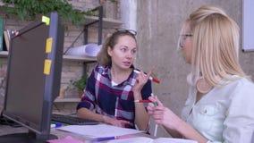 Trabajo, colegas femeninos creativos lindos que discuten para trabajar materias relacionadas en oficina de negocios metrajes