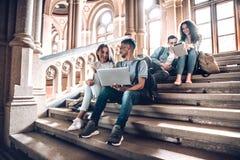 Trabajo con la gente que le motiva e inspira Grupo de estudiantes que estudian mientras que se sienta en las escaleras en univers imagen de archivo
