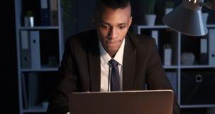 Trabajo confuso del hombre de negocios de última hora en el ordenador portátil de la oficina