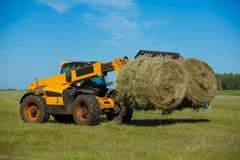 Trabajo cosechando la cosechadora en el campo del trigo fotos de archivo libres de regalías