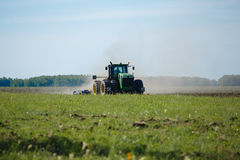 Trabajo cosechando la cosechadora en el campo del trigo imagen de archivo libre de regalías