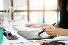 Trabajo creativo de la mujer del diseño gráfico en la tabla con la pluma del ratón fotografía de archivo libre de regalías