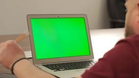 Trabajo creativo del encargado Concepto del asunto Hombre joven confiado en su PC del ordenador portátil con la pantalla del verd metrajes
