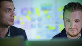 Trabajo de dos hombres jovenes en la oficina en la noche almacen de metraje de vídeo