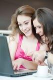 Trabajo de dos muchachas sobre una computadora portátil fotos de archivo libres de regalías