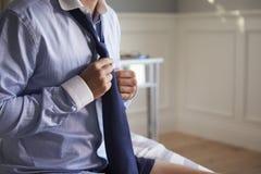 Trabajo de Getting Dressed For del hombre de negocios por la mañana foto de archivo