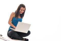 Trabajo de la chica joven sobre la computadora portátil Fotografía de archivo