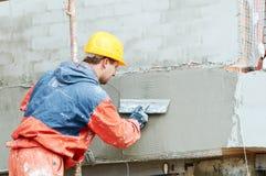 Trabajo de la fachada constructor que enyesa la pared del exterior con el flotador del cuchillo de masilla imagen de archivo libre de regalías