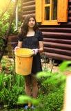 Trabajo de la muchacha del adolescente en el jardín con el compartimiento plástico amarillo Foto de archivo libre de regalías