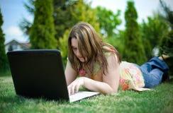 Trabajo de la muchacha sobre la computadora portátil en jardín Foto de archivo