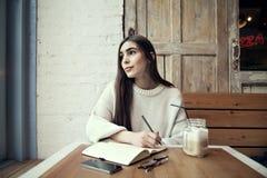 Trabajo de la mujer en café con el ordenador portátil cerca de la ventana con latte del café Fotografía de archivo libre de regalías