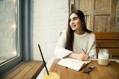 Trabajo de la mujer en café con el ordenador portátil cerca de la ventana con latte del café Fotografía de archivo