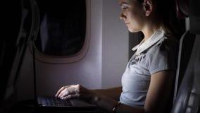 Trabajo de la mujer joven sobre el ordenador portátil en el aeroplano en la noche metrajes
