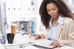 Trabajo de la oficina del Afro ocupado trabajando con el ordenador Fotografía de archivo libre de regalías
